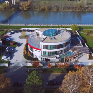 Andel Elite dental center Hlohovec - budova-sidlo stomatologickeho centra -zubna ambulancia - cerveno siva ovalna stavba- R. Dilonga - 920 01 Slovensko-letecky pohlad-dron-fotografia